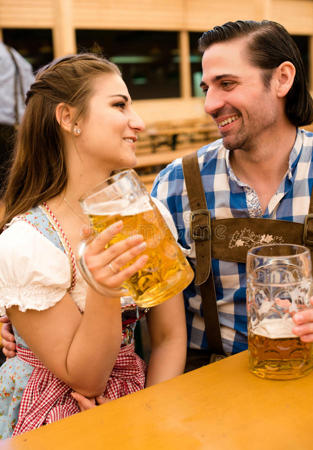 Young couple flirting in Oktoberfest beer tent royalty free stock image
