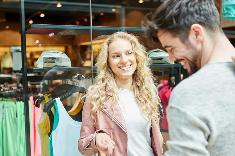 Young couple is flirting while shopping. In front of a fashion store in the mall royalty free stock photo