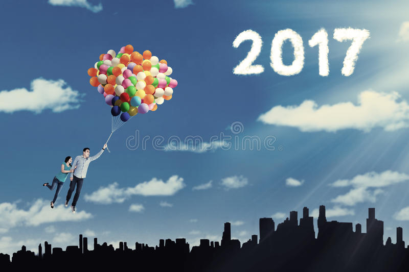 Young couple flying on balloons royalty free stock photos