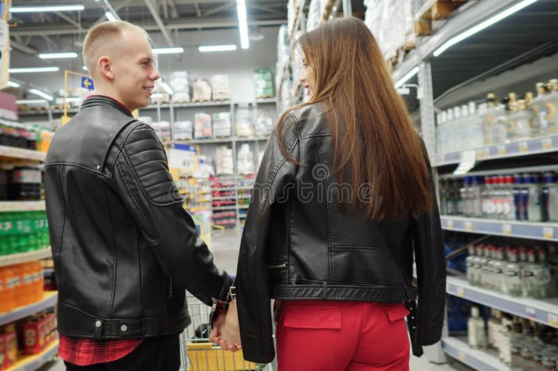 Young couple in food supermarket. Back view stock image