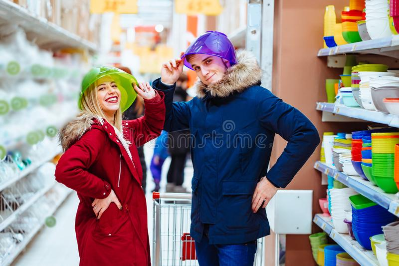 Young couple fooling around with bowls in a supermarket royalty free stock photography