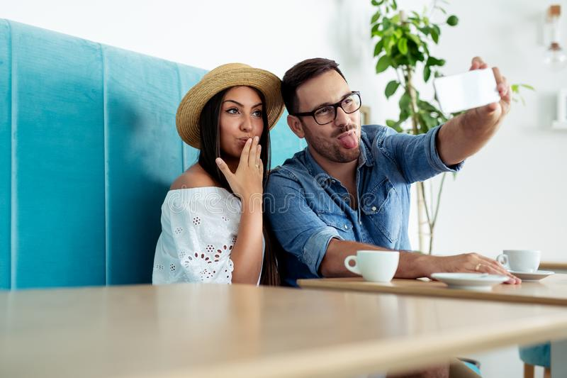 Young couple fooling around, taking selfies. - Image royalty free stock photography