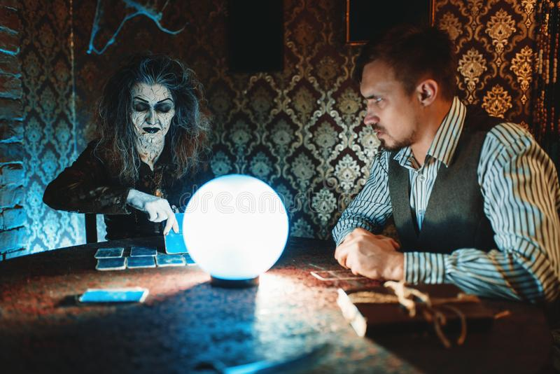 Young couple and fortune teller, spiritual seance. Young couple and fortune teller at the table with crystal ball on spiritual seance, scary wizard reads the royalty free stock photos