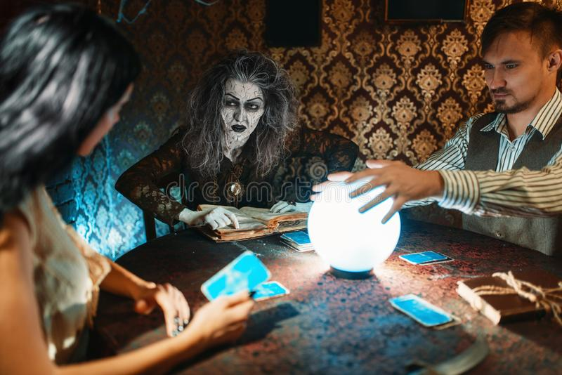 Young couple and fortune teller, spiritual seance. Young couple and fortune teller at the table with crystal ball on spiritual seance, scary wizard reads the royalty free stock photography