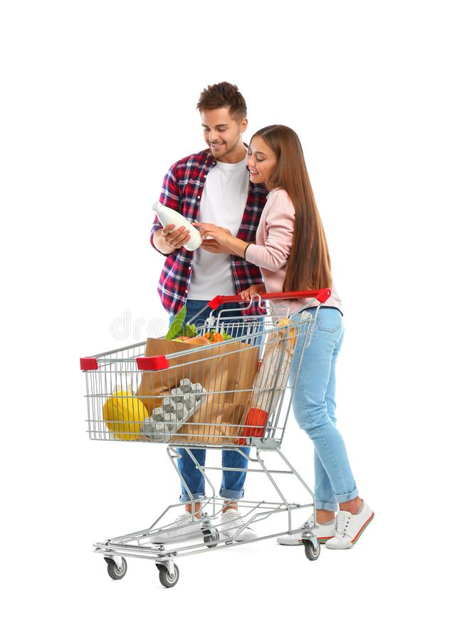 Young couple with full shopping cart on  background. Young couple with full shopping cart on white background stock photos