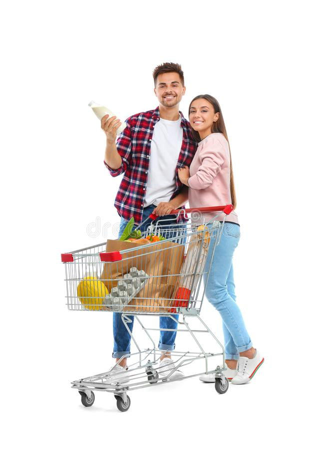 Young couple with full shopping cart on background. Young couple with full shopping cart on white background stock photography