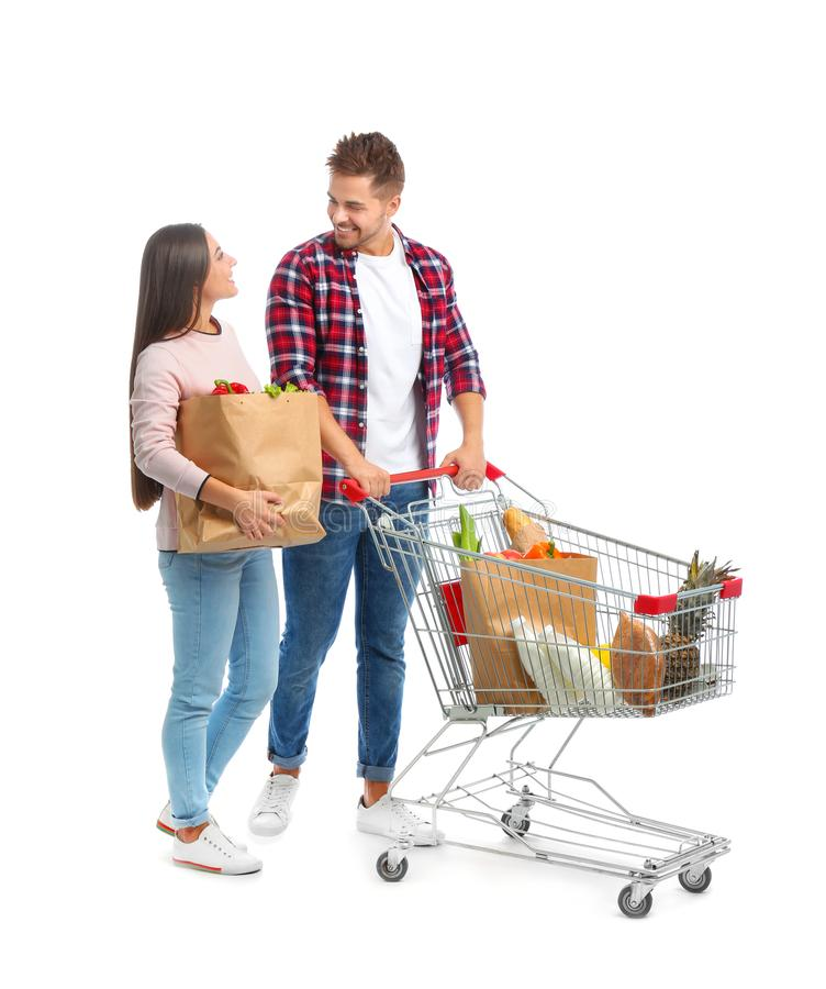 Young couple with full shopping cart and paper bags on background. Young couple with full shopping cart and paper bags on white background royalty free stock image