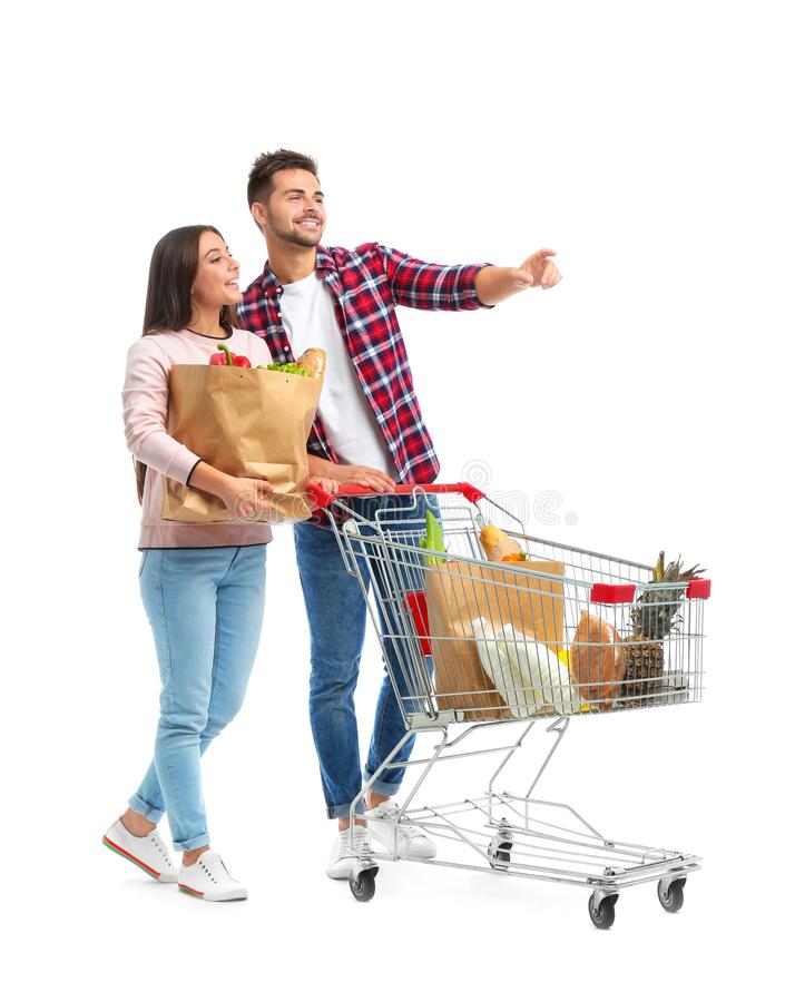 Young couple with full shopping cart and paper bags on background. Young couple with full shopping cart and paper bags on white background royalty free stock photography