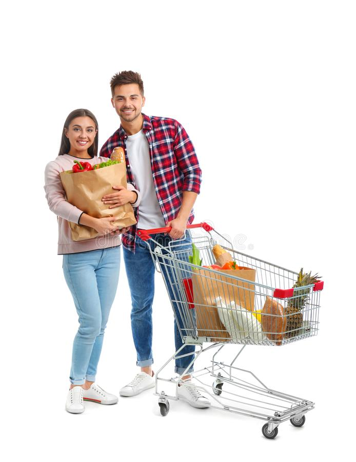 Young couple with full shopping cart and paper bags on background. Young couple with full shopping cart and paper bags on white background royalty free stock images