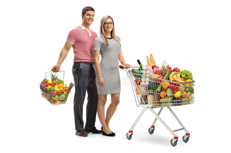 Young couple with a full shopping cart and a shopping basket. Isolated on white background royalty free stock images