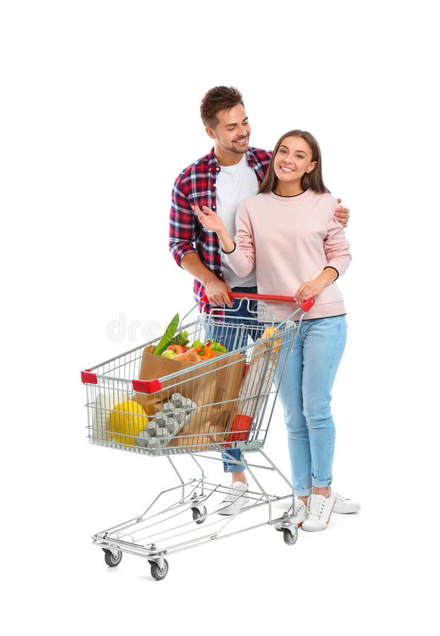 Young couple with full shopping cart on background. Young couple with full shopping cart on white background royalty free stock photos