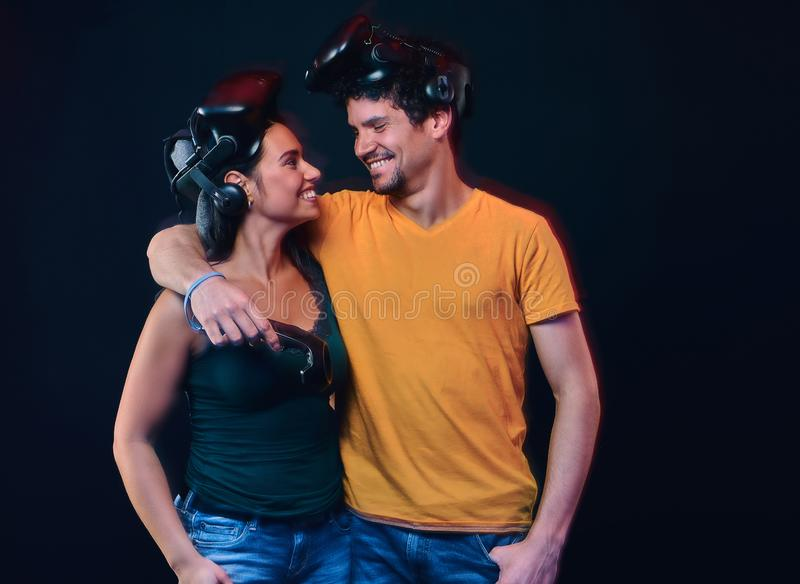 Young couple of gamers wearing virtual reality goggles hug and look at each other. Isolated on dark background royalty free stock photos