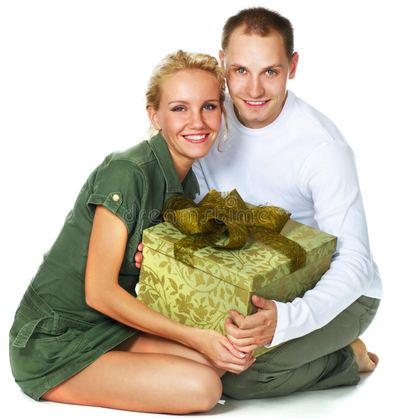 Young couple with a gift. Happy young couple with a gift over white royalty free stock photos