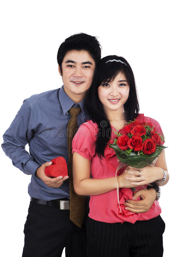 Young couple with gift and flowers. Attractive young couple with a gift and flowers - isolated on the white background royalty free stock photos