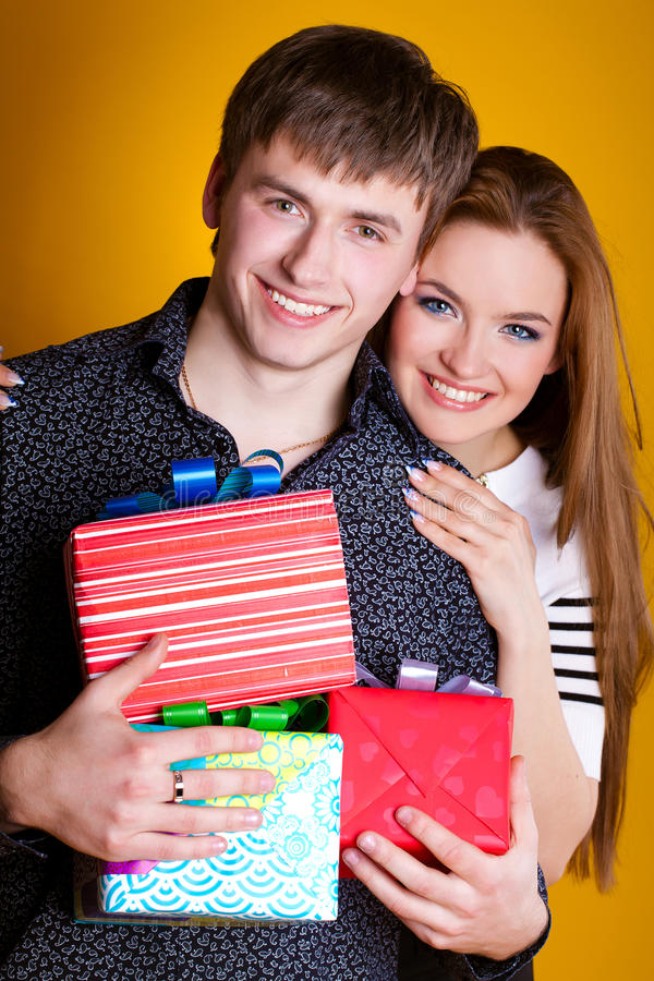 Young couple with gifts on yellow royalty free stock photo