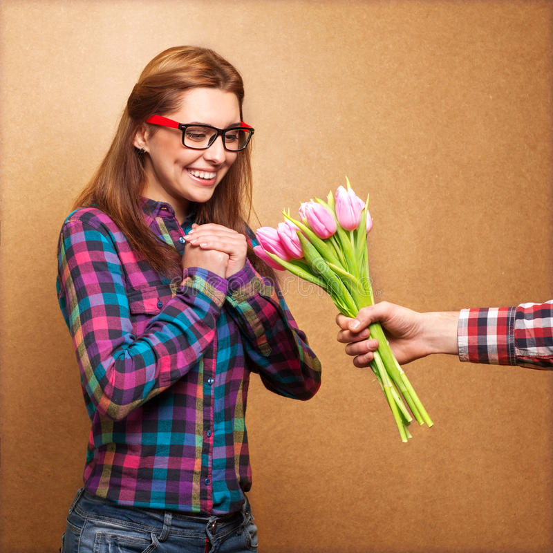 Young couple. Girl wearing hipster surprised donation of a bouquet of flowers stock image