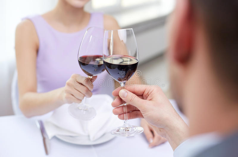 Young couple with glasses of wine at restaurant. Restaurant, people, celebration and holiday concept - close up of young couple with glasses of red wine at royalty free stock images