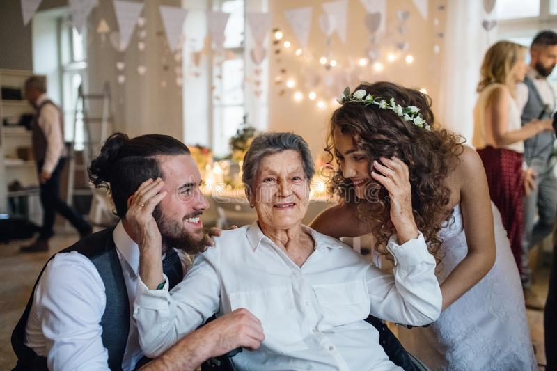 A young couple with grandmother on a wedding, posing for a photograph. royalty free stock photo