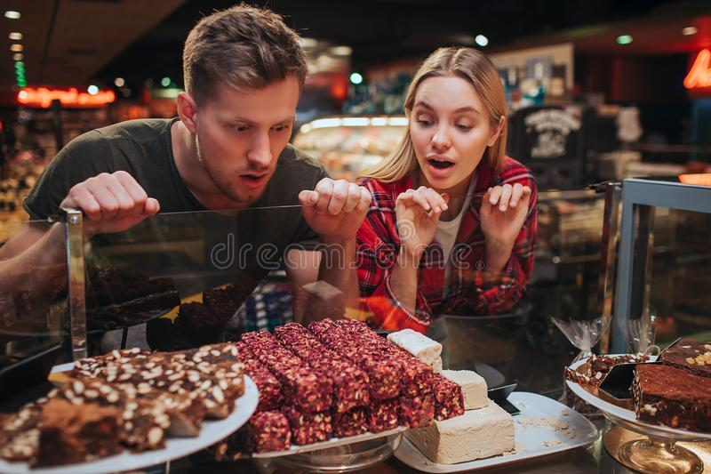 Young couple in grocery store. Hungry man and woman look at sweets on shelf with amazing sight. They want to eat it stock images