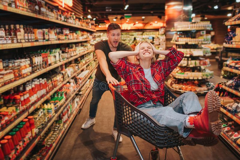 Young couple in grocery store. They play together. Woman sit in trolley and keep eyes closed. Guy scream behind and let stock image