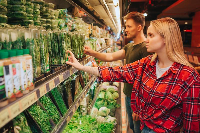 Young couple in grocery store. They stand in front of herbs shelf and pick them together. Serious concentrated people in. Store royalty free stock photos