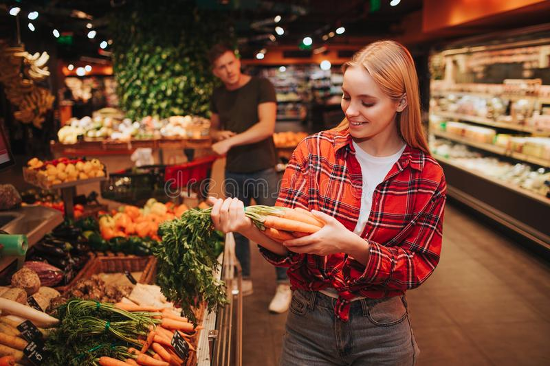 Young couple in grocery store. Woman stand in front and hold carrot in hands. She look at it and smile. Young man stand. Young couple in grocery store. Woman stock images