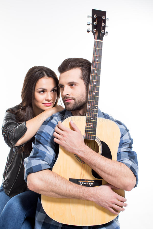 Young couple with guitar. Beautiful young couple with acoustic guitar isolated on white stock photography