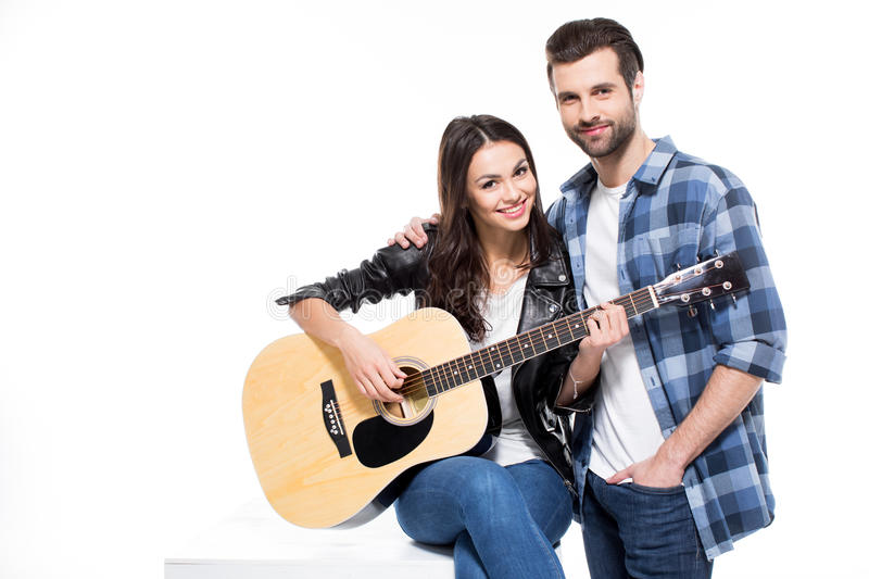 Young couple with guitar. Beautiful young couple with acoustic guitar smiling at camera on white stock photo