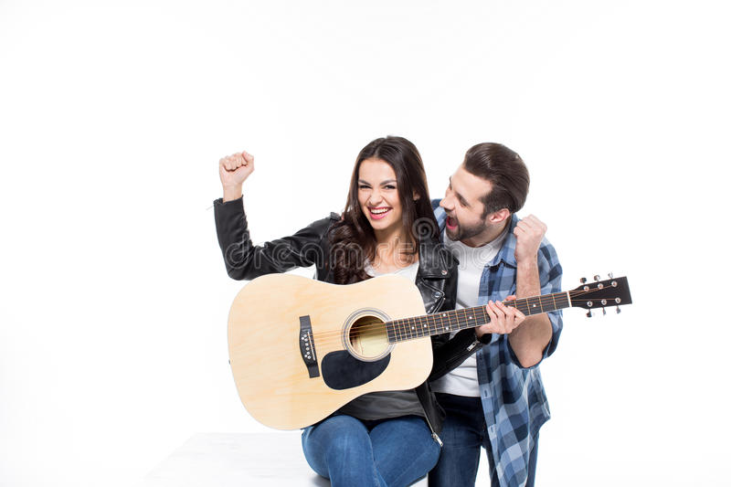 Young couple with guitar. Excited young couple sitting with guitar and triumphing on white royalty free stock photography