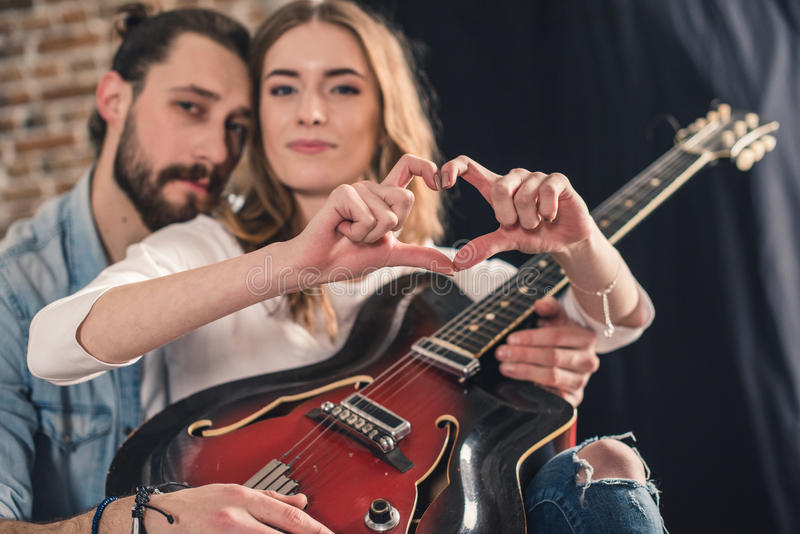 Young couple with guitar. Young couple holding guitar and women shows heart sign with fingers stock images