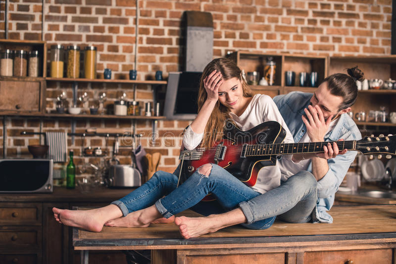 Young couple with guitar. Young couple sitting on the kitchen table and holding guitar royalty free stock image