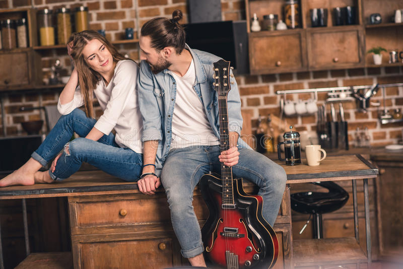 Young couple with guitar. Young couple sitting on kitchen table and men holding guitar royalty free stock photo