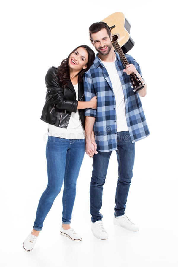 Young couple with guitar. Smiling young couple with acoustic guitar isolated on white royalty free stock photo