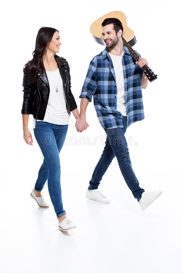 Young couple with guitar. Smiling young couple holding hands and looking at each other while walking with guitar royalty free stock photos