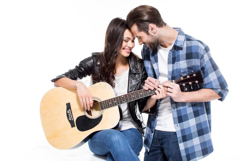 Young couple with guitar. Smiling young couple touching foreheads while playing acoustic guitar stock images