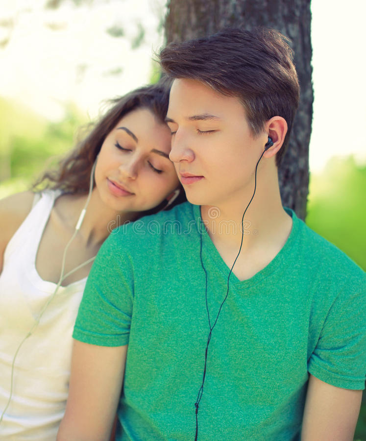 Young couple guy and girl listens to music in a headphones at park stock photography