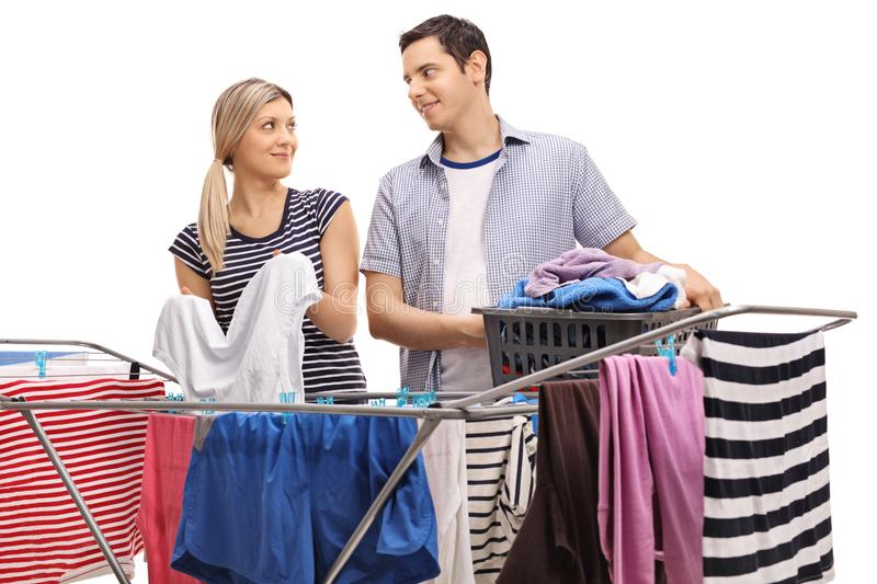 Young couple hanging clothes on a rack dryer together stock images