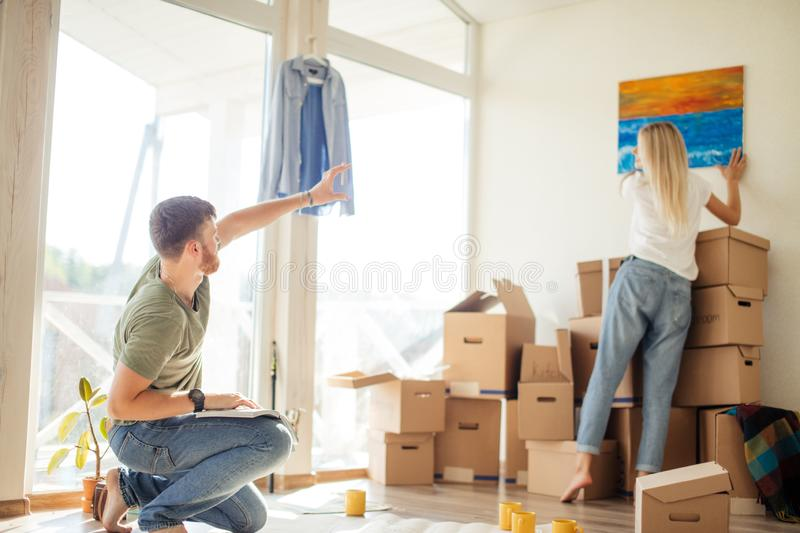 Moving house. Couple hanging picture on wall in new home stock photo