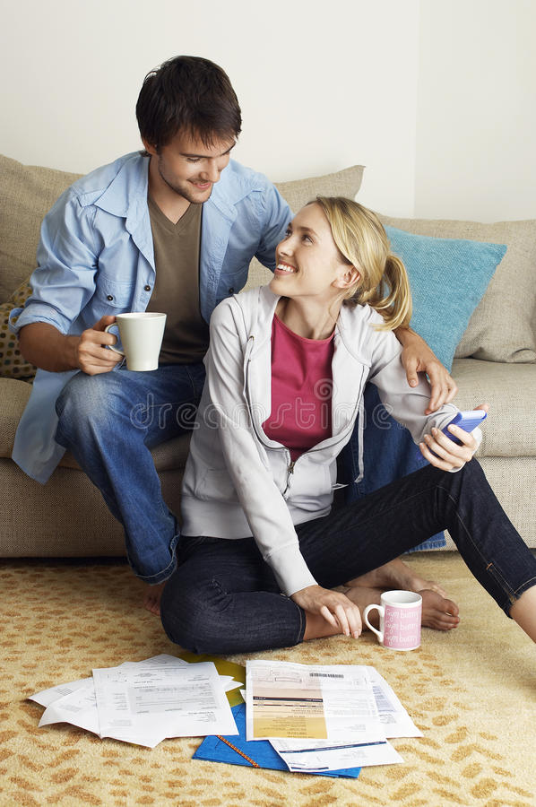 Young Couple Happily Calculating Expenses royalty free stock photography