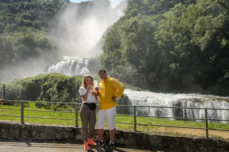 A young couple - happy family are drinking coffee in a cafe on the background of a waterfall Cascata delle Marmore in Italy stock image
