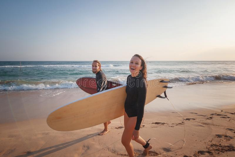 Young couple happy smiling surfers on ocean coast, sport active lifestyle vacation travel concept. Young couple of happy smiling surfers on ocean coast, sport stock photo