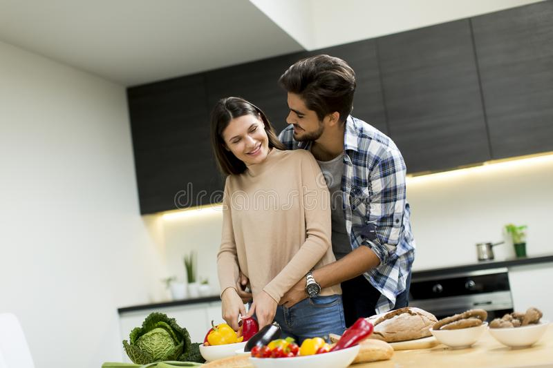 Young couple have fun in modern kitchen indoor while preparing v stock images