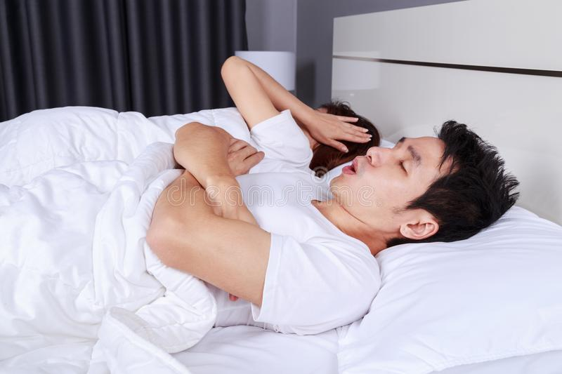 Couple have problem with man`s snoring on bed stock photo