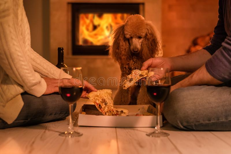Young couple have romantic dinner with pizza and wine over fireplace background. stock images