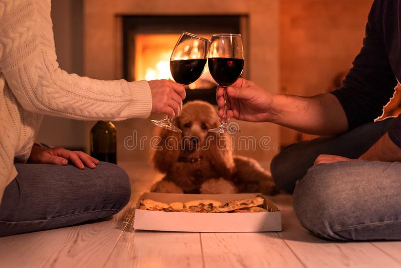 Young couple have romantic dinner with pizza and wine over fireplace background. royalty free stock photos
