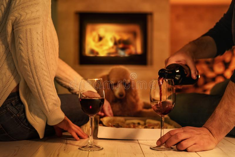 Young couple have romantic dinner with pizza and wine over fireplace background. royalty free stock photography