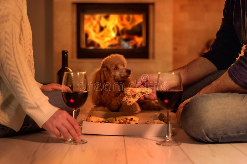 Young couple have romantic dinner with pizza and wine over fireplace background. stock image