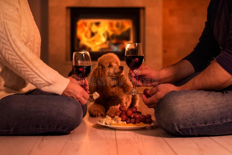 Young couple have romantic dinner with wine over fireplace background. royalty free stock images