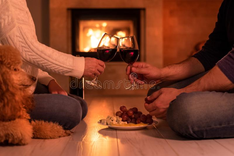 Young couple have romantic dinner with wine over fireplace background. stock photography