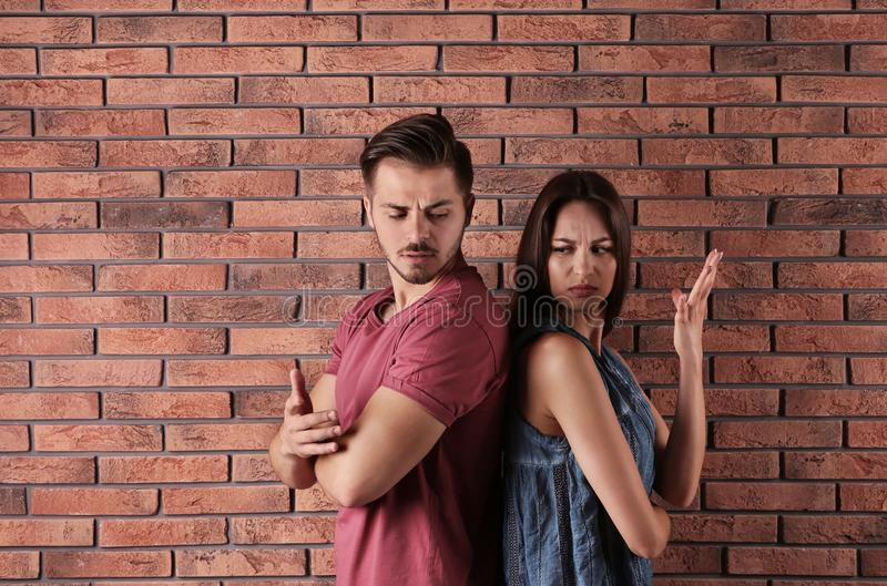 Young couple having argument near brick wall stock image